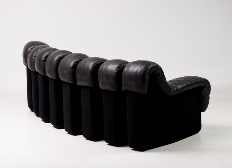 Iconic vintage DS 600 nonstop sectional leather sofa designed by Heinz Ulrich, Ueli bergère and Elenora Peduzzi-Riva and manufactured by De Sede. The sofa sections consist of original black leather and black felt bases. The distressed leather shows