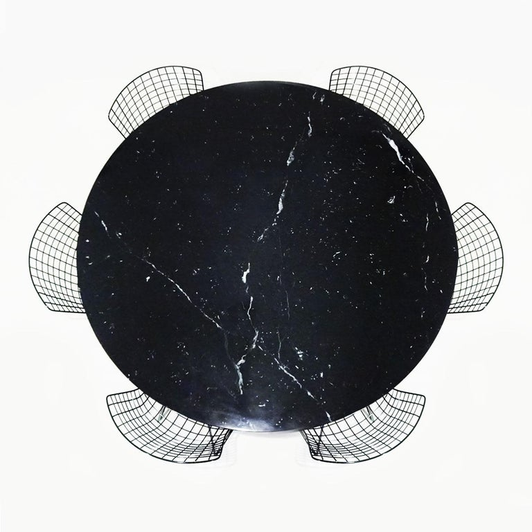 A Classic midcentury dining set comprising an original black Nero Marquina marble Eero Saarinen round tulip dining table matched to 6 original black Harry Bertoia wire chairs with original seat pads, both produced by Knoll.  This is a Classic