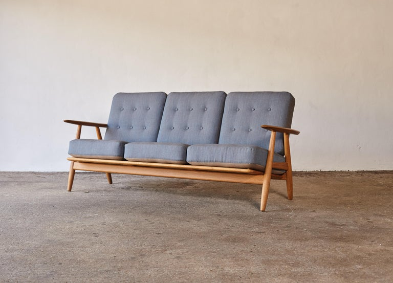 An oak GE-240 cigar sofa designed by Hans J. Wegner and produced by GETAMA, Denmark. The oak frame is in excellent vintage condition. Original sprung cushions, newly upholstered in Kvadrat fabric.      UK customers please note: displayed