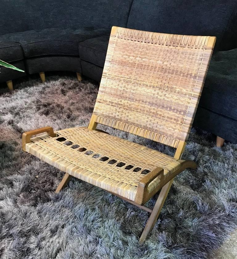 Iconic in design and aesthetic. This exquisite folding chair was designed by famed Danish designer Hans Wegner and is in its original finish and cane seat and back. The chair has the authentic burned in mark and stamp (