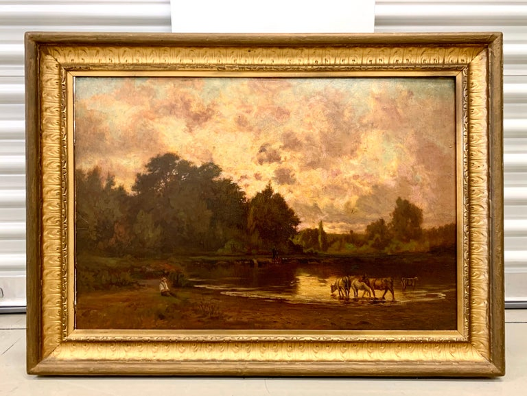 Beautiful pastoral landscape oil painting with cows on a river beneath a purple sky. Oil on board. Signed on back along with provenance. Displayed in a gold giltwood frame, late 19th century.