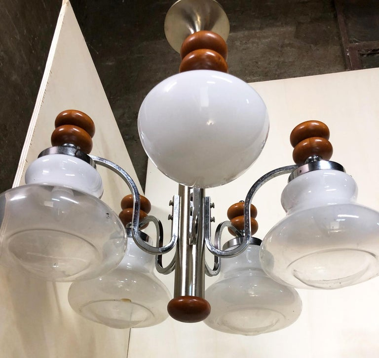 Original Italian five-light chandelier, from 1970, chrome, wood and glass. One of the five glass lampshades is of a different shape and completely white The fixture requires five European E14 candelabra bulb In working condition We recommend