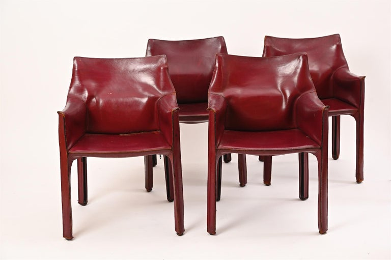 Four original Mario Bellini for Cassina Cab armchairs in Burgundy red.  Stitched leather with zips over steel frame structure.  Leather is nicely worn with good patina.  Some marks and scratches to leather. No tears. Structurally sound. And