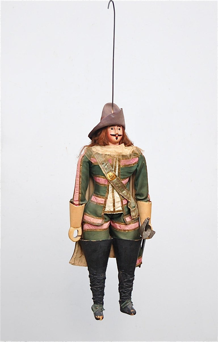 This fully handmade, characterful Musketeer Toone puppet is still wearing his original period costume in green with pink ribbon highlights. The fabric is in excellent vintage condition. He is wearing a plumed wide-brimmed cavalier hat in felt which