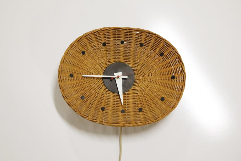 Out of the 150+ designs created by George Nelson for Howard Miller, this Oval 'Basket' wall clock is one of the more rare editions. Small black circles mark the number positions around the oval, woven wicker-basket clock face. From the center, the