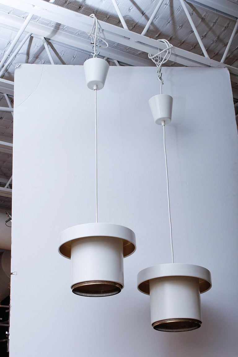 Near pristine pair of original production Alvar Aalto Model A301 ceiling pendants, manufactured by Valaistustyo¨ Ky, Finland, circa 1955. Interior impressed stamp with manufacturer's mark and model number. Enameled metal with brass detailing.