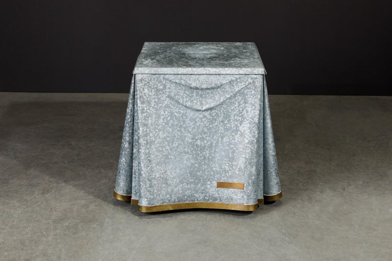 This exceptionally rare and high-sought after collectors item is the John Dickinson model #107 drape end table with trompe-l'œil fabric motif in galvanized steel and brass binding. This piece of functional fine art is suited for a design collector,