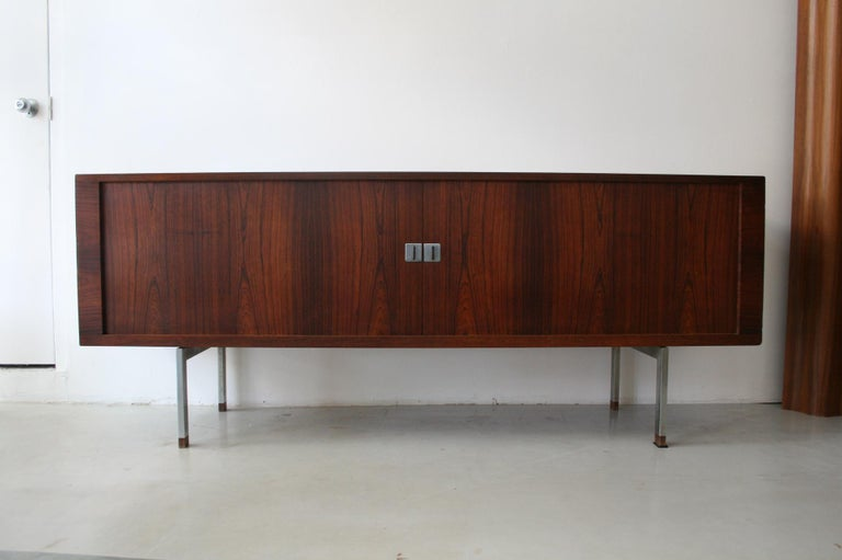 A beautiful rosewood grain case on brushed steel legs with rosewood tips. Features 2 rosewood 'tambour' doors that slide on a hidden track to disappear when opened. Inside are oak adjustable shelves and drawers for storage options.  Produced by Ry