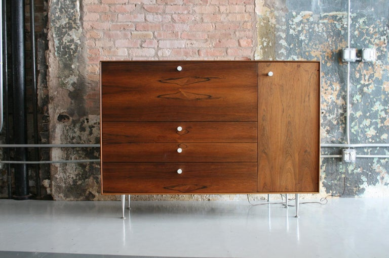 This is a Thin Edge Series secretary cabinet / desk designed by George Nelson for Herman Miller. Named for its clean lines, the minimal Rosewood case floats on aluminum champagne flute legs and finished with Nelson's signature porcelain knobs. Panel