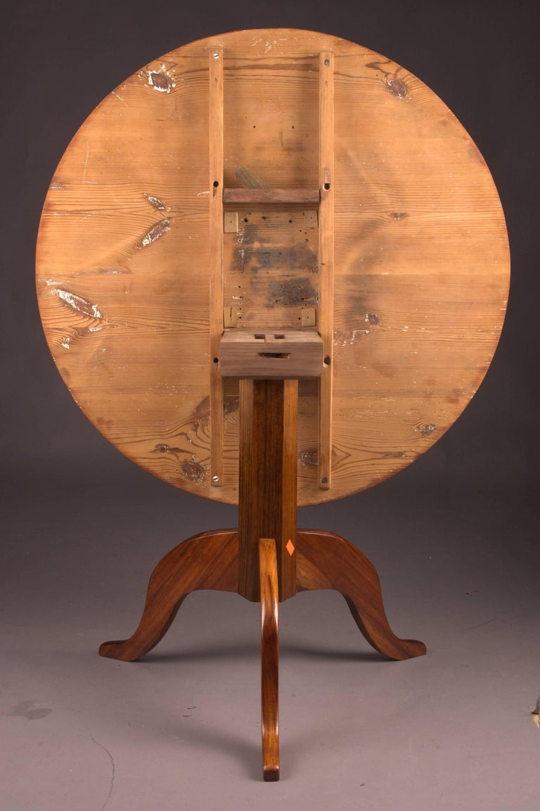 Mahogany on solid wood. Eightfold bent column shaft. Beneath it there are three volute-shaped curved legs. Straight cheeks for round tabletop. A strict form of early-Biedermeier time. It is equipped with a folding mechanism. This table was