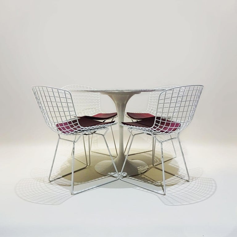 A classic mid century dining set comprising an original white marble Eero Saarinen round tulip dining table matched to 4 x white Harry Bertoia wire chairs with original seat pads.