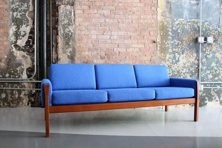 Original Hans Wegner design in teak and redone in a blue Maharam wool upholstery. All strapping and foam has been replaced and the frame has been restored to its original finish.