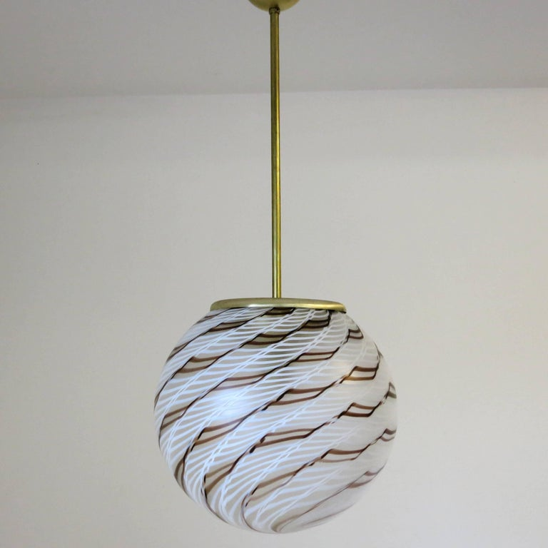 Original vintage pendant with clear Murano glass globe and artistic chocolate brown and vanilla white stripes spiral design on unlacquered brass frame by La Murrina Made in Italy in the 1960s One light / E26 type / max 60W Measures: Diameter 15.75
