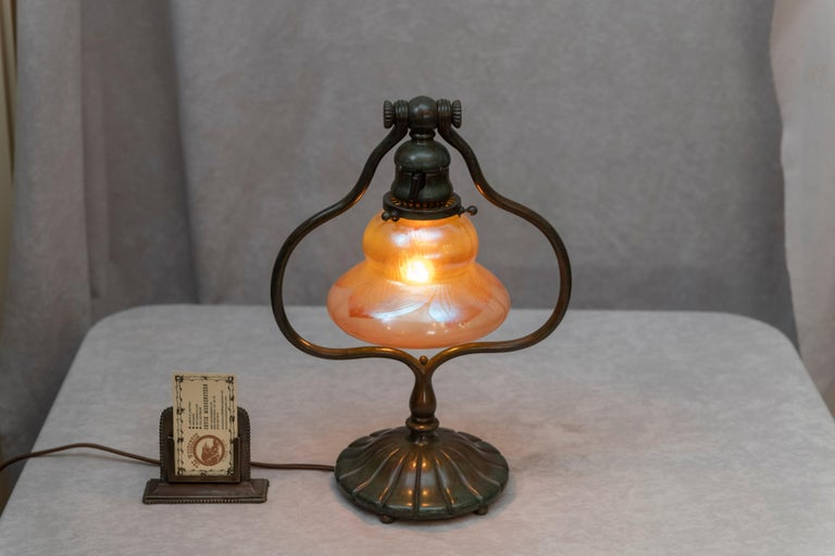 This is a real Tiffany Studios Lamp. The bronze base which supports the shade can be adjusted to the angle of your preference, circa 1905. The shade is signed