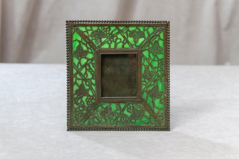 This smaller example of Tiffany's typical picture frame is a fine example of the genius of the man. Done in the pine needle pattern with green glass and finished in a rich warm patination to the metal. A lovely choice frame that can be fitted in