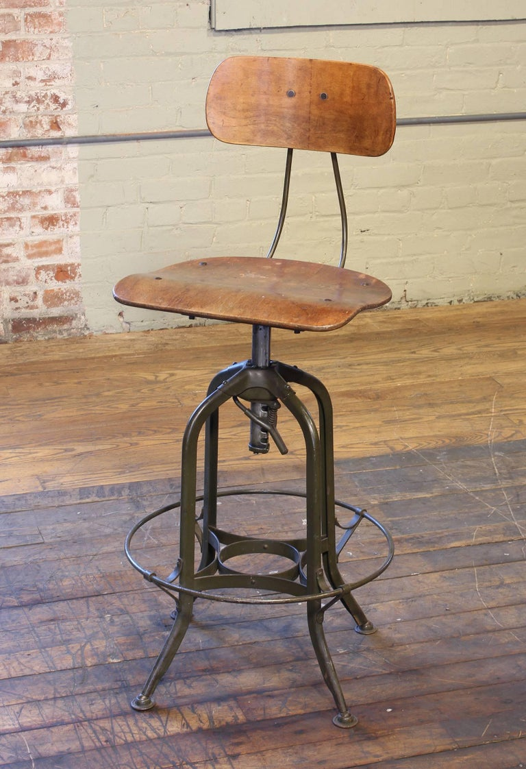 Authentic original adjustable Toledo bar stool. Bent plywood seat and back, distressed military green painted steel frame. Seat ring diameter measures 18