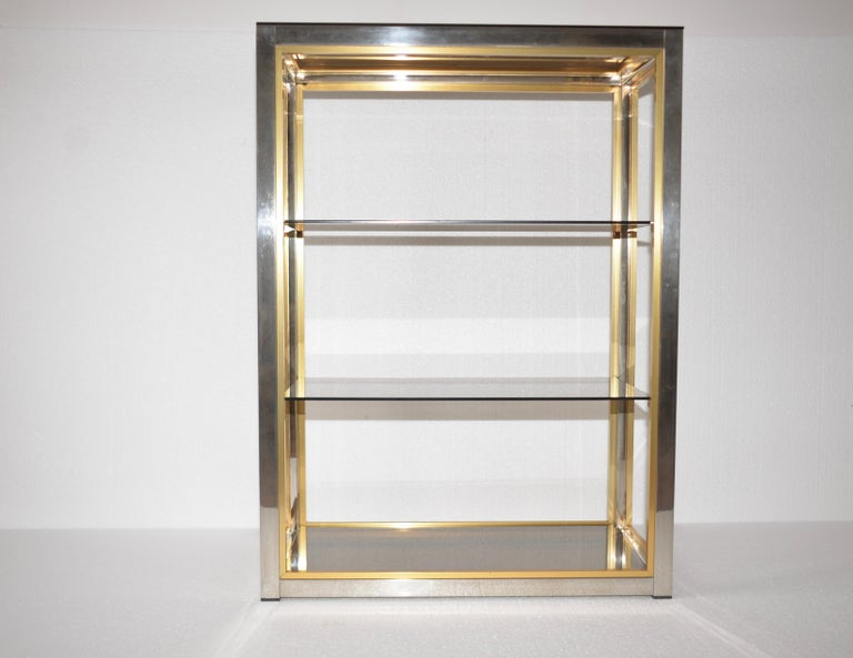 An original Italian chrome shelving unit designed by Renato Zevi for Romeo Rega. A lovely item with four shelves within a polished chrome frame and it is also edged in brass in the Hollywood Regency Style. An iconic piece well know and documented in
