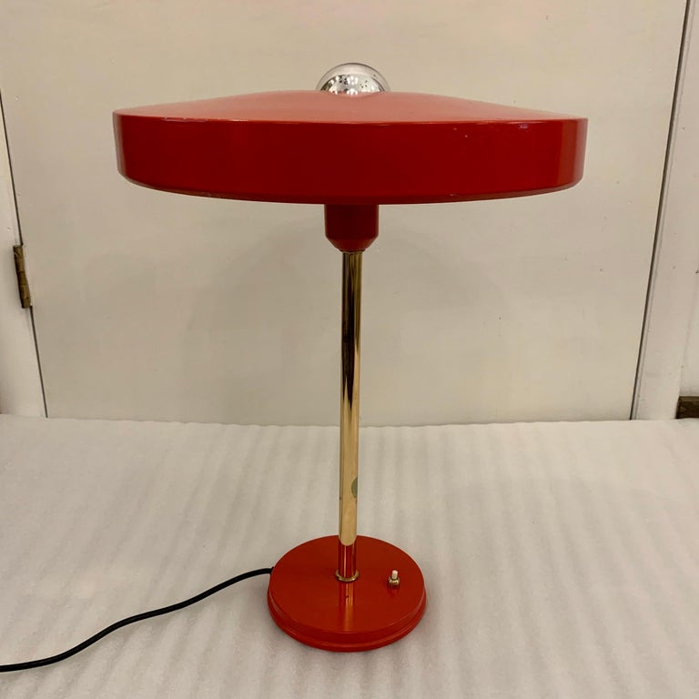 ALL original Louis Christiaan Kalff for Philips red table lamp, 1950s. Featuring round red enameled shade, brass stem and round 6 inch diameter base with original base switch. Shown with mercury bulb and Stamped by famed Dutch manufacturer, Philips.
