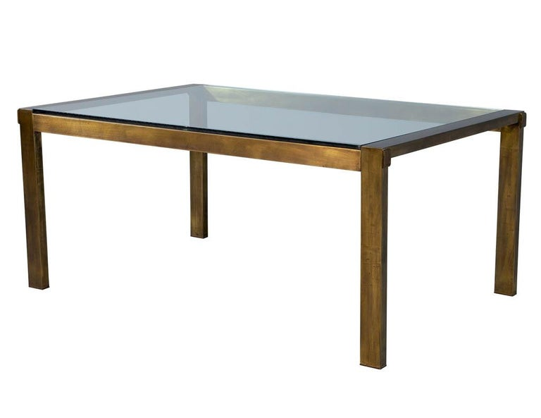 Original vintage Mastercraft aged brass dining table. Rich patinated finish with original glass top and glass pullout extensions. Includes wooden crate for leaf storage. Original glass does have minor wear consistent with age and use.   Table