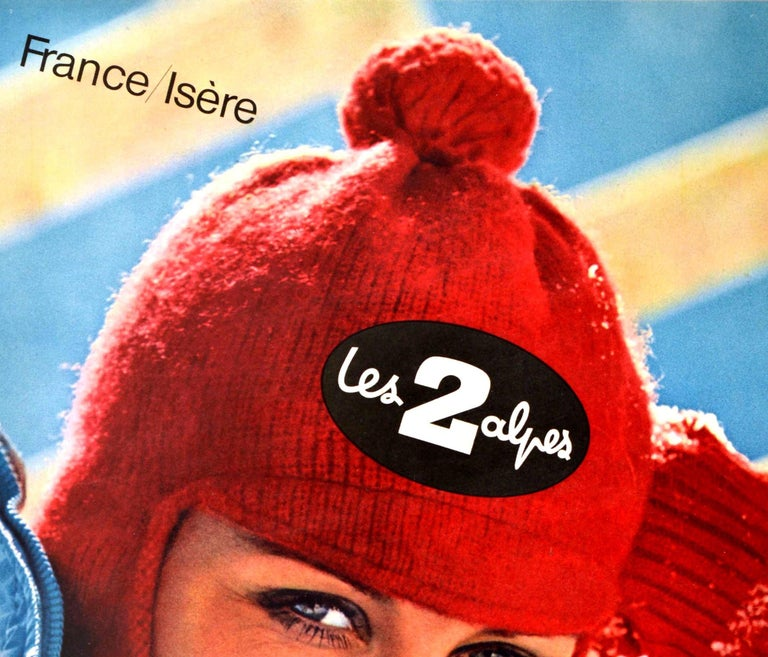Original vintage winter sport travel poster for France Isere Les 2 Alpes ski resort featuring a great photograph of a lady wearing red wool balaclava hat and gloves and a blue ski jacket resting on the snow and smiling to the viewer. The popular