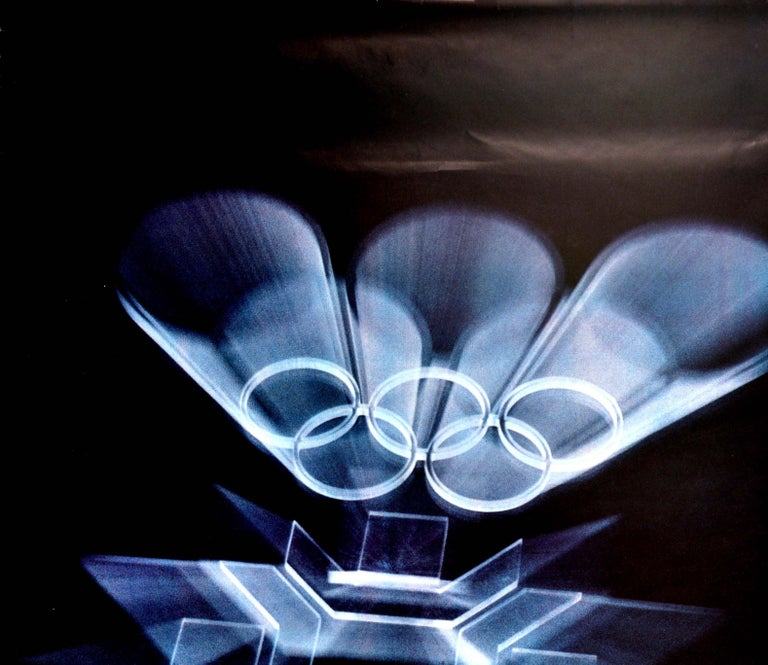 Original vintage winter sports poster for the XIV Olympic Winter Games Sarajevo 1984 Yugoslavia featuring a dynamic design of the Olympic Rings and 1984 Winter Olympics logo in silver shining on a black background, the emblem symbolising a stylised