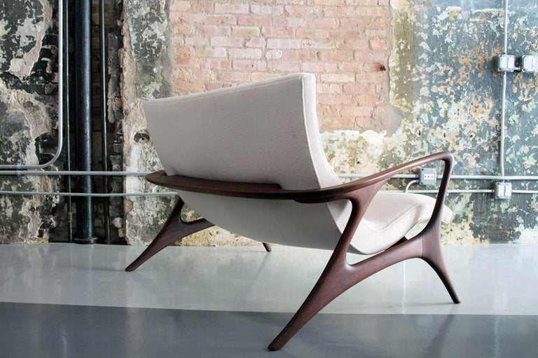An organic sofa or settee or loveseat by Vladimir Kagan. A beautiful sculpted walnut frame cradles a curved seat redone in a high-end cream color Mohair.  This example was produced in the studio of Vladimir Kagan in the 1970s.