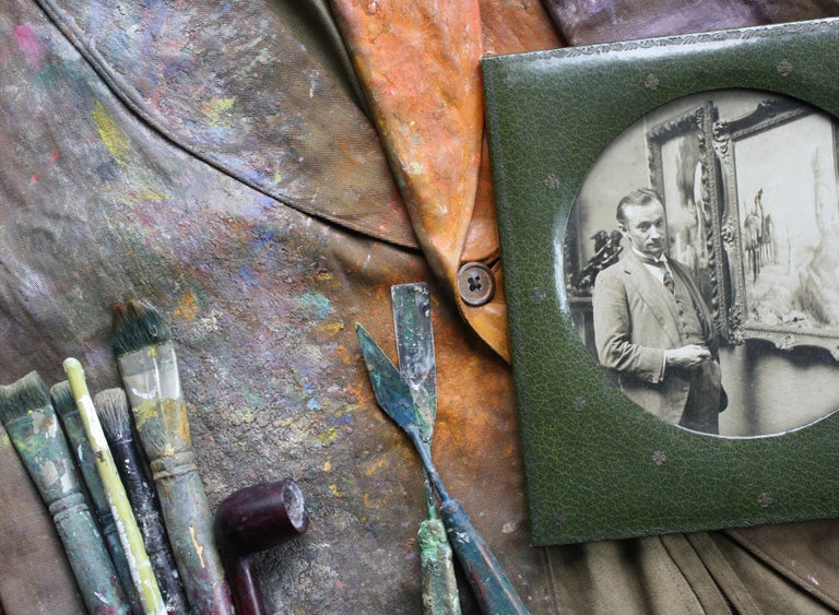 A rather decorative canvas painting jacket used by Orlando Greenwood, with large sections of paint residue/build-up, the piece also is being sold with Greenwoods Bakelite pipe (that can be seen in the photograph) and a sepia photograph of the artist