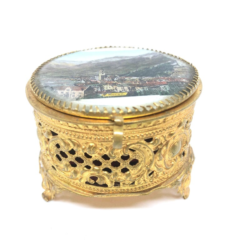 A gorgeous glass top trinket box made of ormolu. The hinged top featuring a City view of Meran. No restoration has been carried out on this charming little trinket box, which remains in very stabile and functioning condition, wear is consistent with
