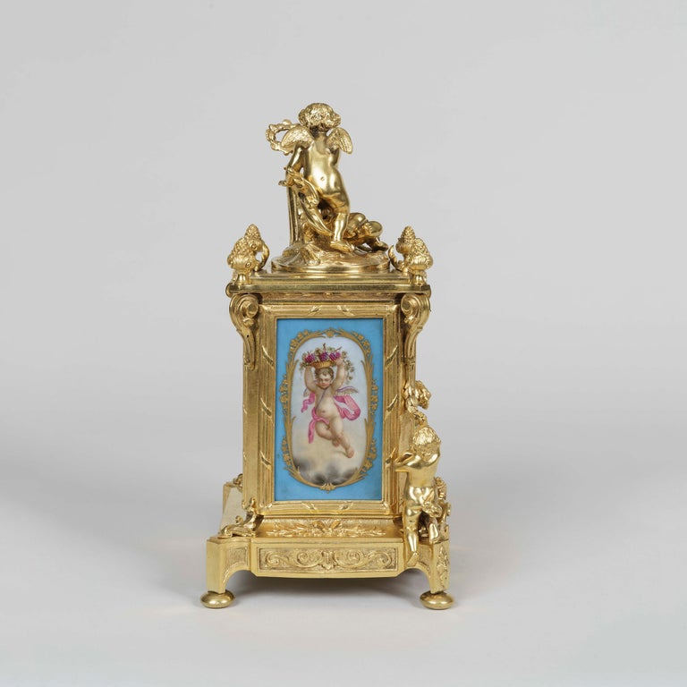 A clock garniture in the Louis XVI Manner By Le Roy et Fils  The ormolu clock case and accompanying candelabra dressed with blue 'Sevres' style hand decorated polychrome panels to the face and sides, depicting amorini, flowers, and musical