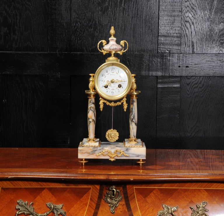 A beautiful original antique French portico clock, Louis XVI style, circa 1880. It is modelled in a stunning variegated specimen marble, salmon pink and silver blue veining, and is mounted with ormolu (finely gilded bronze). The movement is held