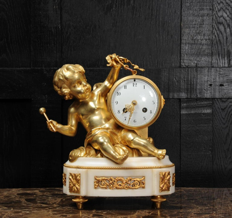 A superb original antique French clock, circa 1880. It is finely modelled in the Rococo manner with a putti floating in the clouds holding the clock modelled as a drum by a ribbon. In the other hand he is about to beat the drum. Beautifully made and