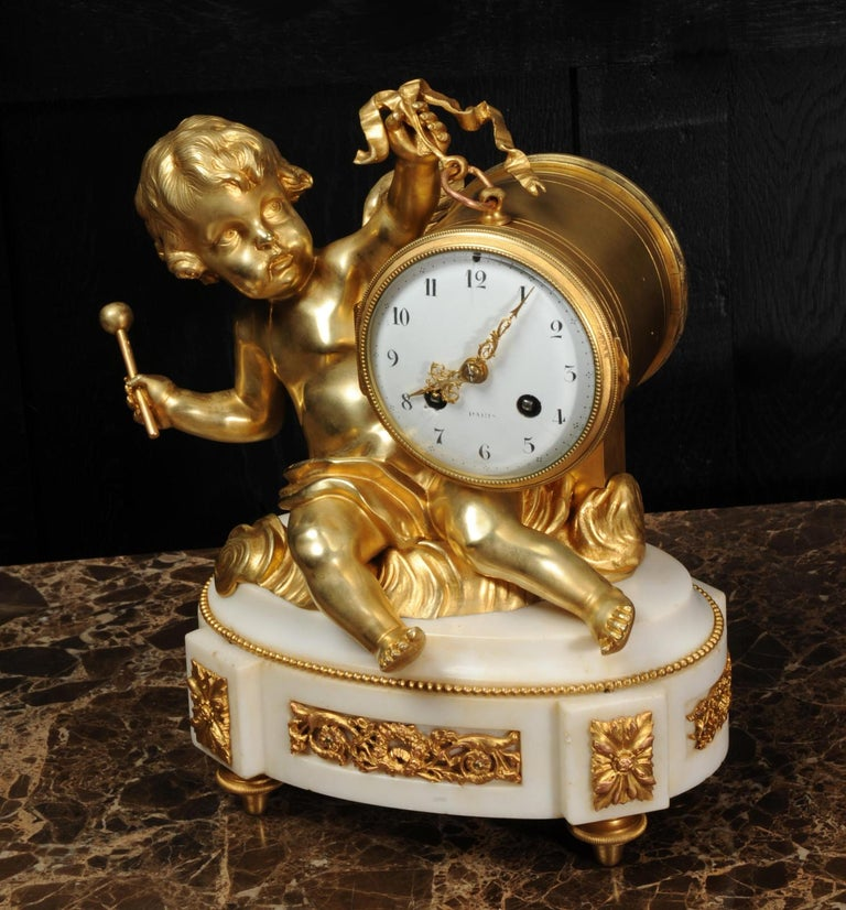 Rococo Ormolu and White Marble Antique Clock, Putto Floating in Clouds Playing a Drum For Sale