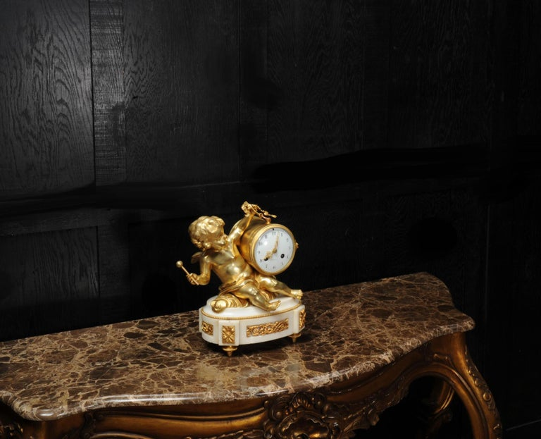 French Ormolu and White Marble Antique Clock, Putto Floating in Clouds Playing a Drum For Sale