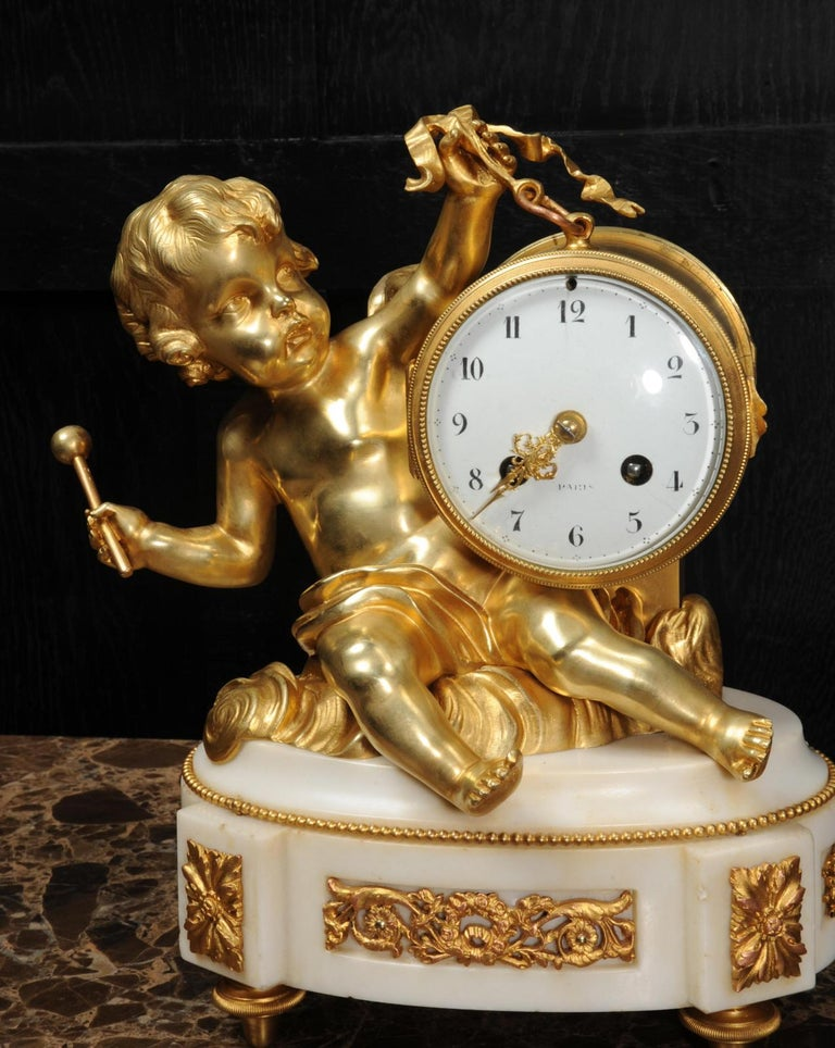 Bronze Ormolu and White Marble Antique Clock, Putto Floating in Clouds Playing a Drum For Sale