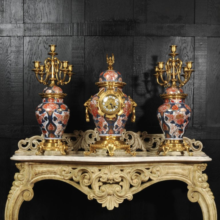 A very large, rare and impressive original antique clock set. The bodies are stunning Japanese Imari Porcelain mounted with finely gilded bronze. Candelabra are formed from a matching pair of Japanese Imari Porcelain jars of inverted pear form