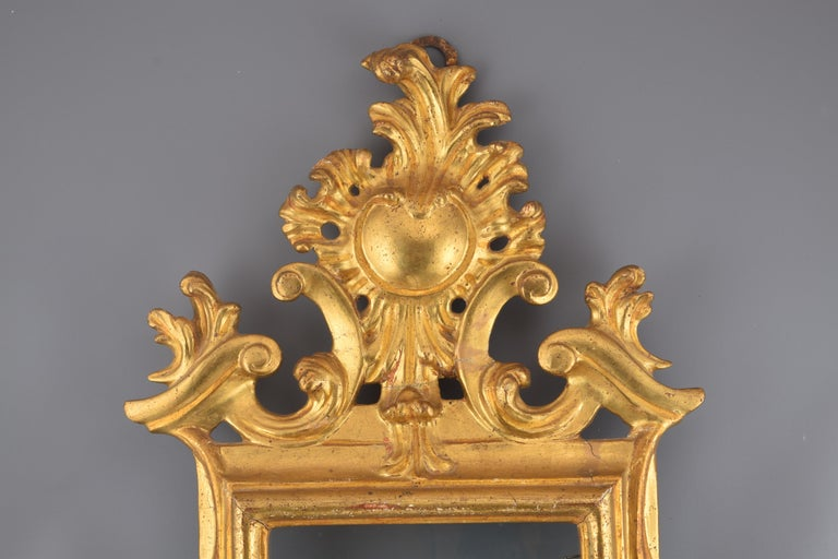 It requires restoration. Rectangular cornucopia with carved and gilded wooden frame decorated with a series of smooth moldings and with a very elaborate finish on the upper part (arranged in symmetrical composition, architectural and vegetal