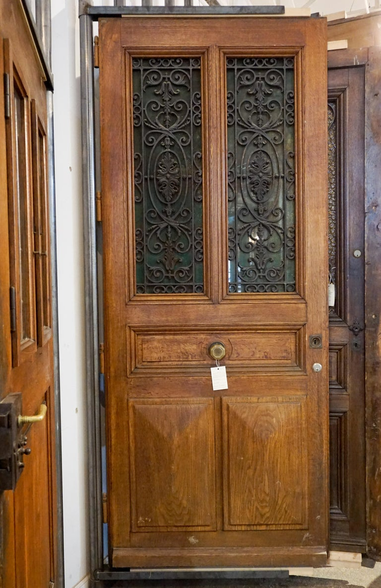Here we have a beautiful antique oak entry door from France. Beautiful cast iron panels and center knob enhance this exquisite European door, circa 1880.  Measurements are: 41.25 x 102.5.