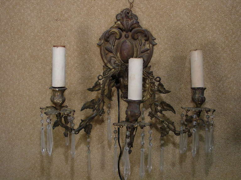 This bronze Rococo wall sconce features three arms. Each of the three arms are entwined with bronze vines and leaves that extend from the ornate wall mount. The light fixtures themselves feature prismed crystal pendants.