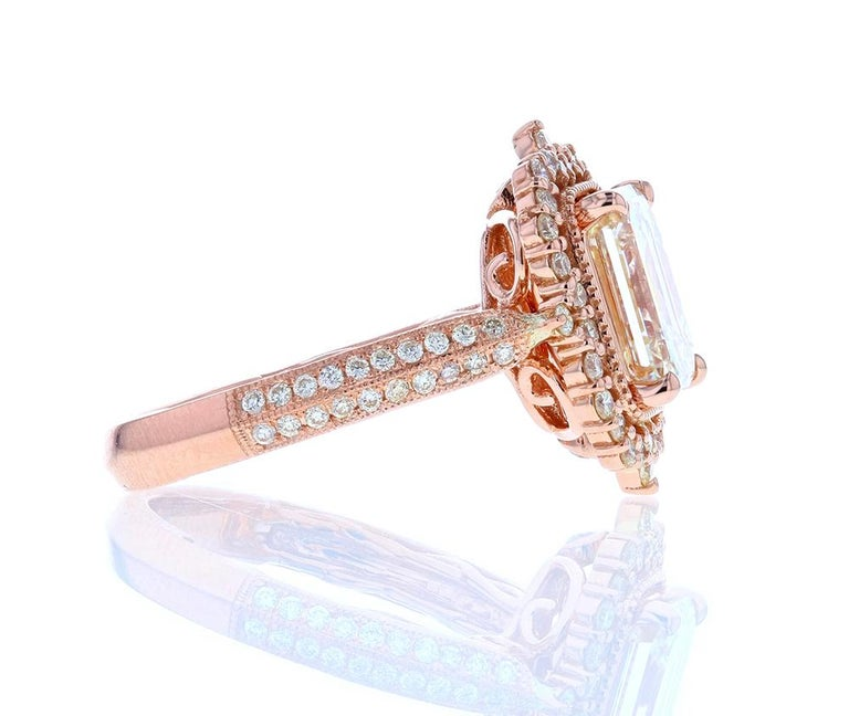 This jaw-dropping diamond engagement ring features a large emerald cut center diamond set in rose gold surrounded by layers and layers of an ornate design with diamond pave. An undulating design on the underside of the basket features a cascade of