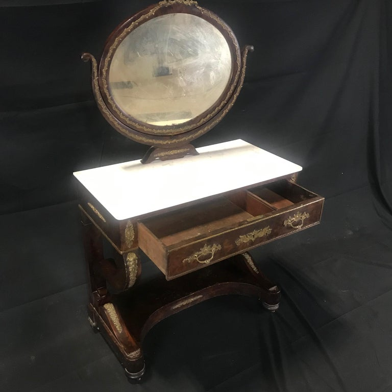 A French Charles X Empire period mahogany dressing table with original marble top and gorgeous bronze decoration. Some losses to the veneer (see photos). All original. #5707 Measures: H skirt 24.25