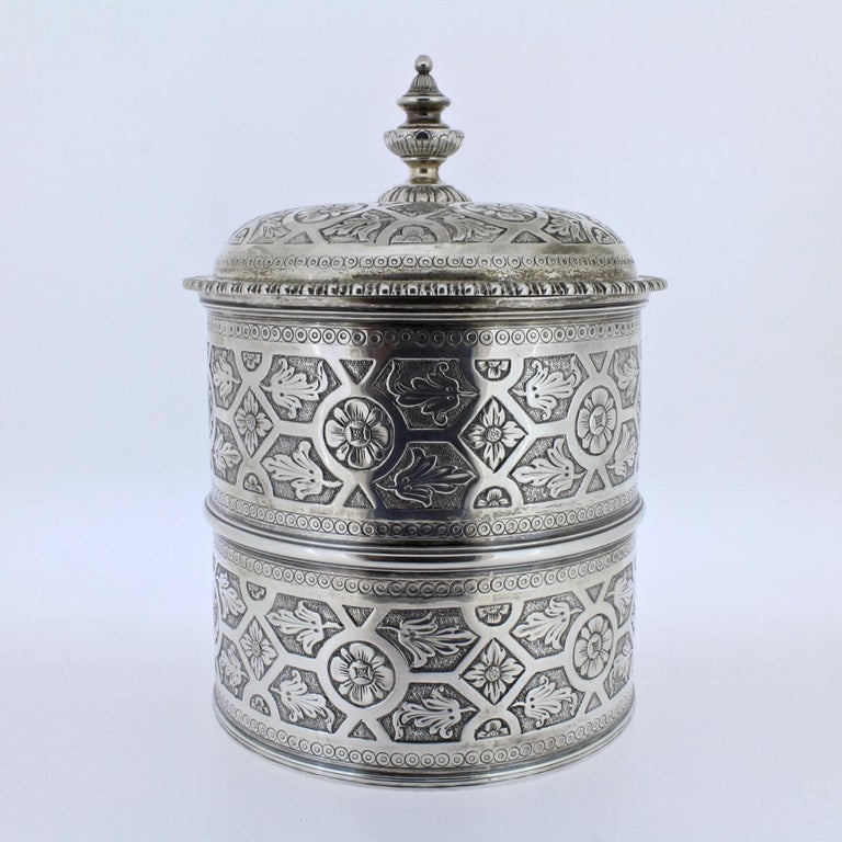 A wonderfully detailed Portuguese covered dresser jar (or humidor) in solid silver by Sarmento, the renowned Portuguese jewelers and silversmiths.  A domed and gadrooned lid covers the two-sectioned body of this jar. Both cover and jar have