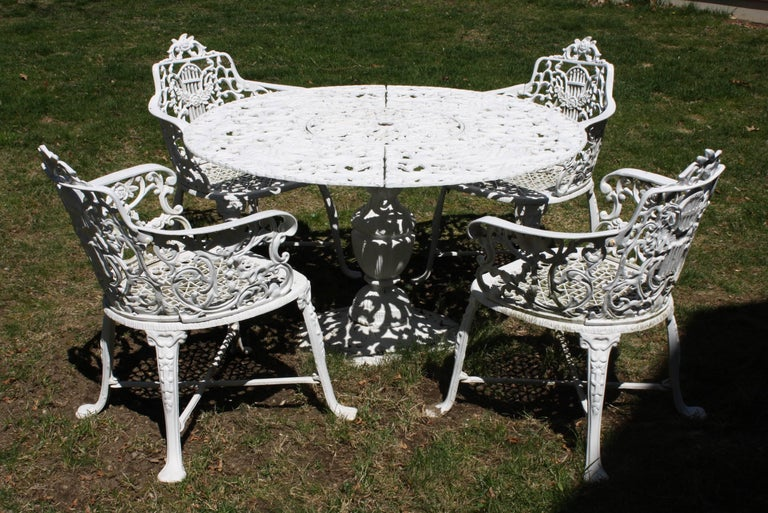 Wonderful ornate Victorian style garden dining set comprising a table and four armchairs. The set is made of cast aluminum so it is light and easy to move, and will not rust (this set has none of the care and maintenance associated with cast iron).