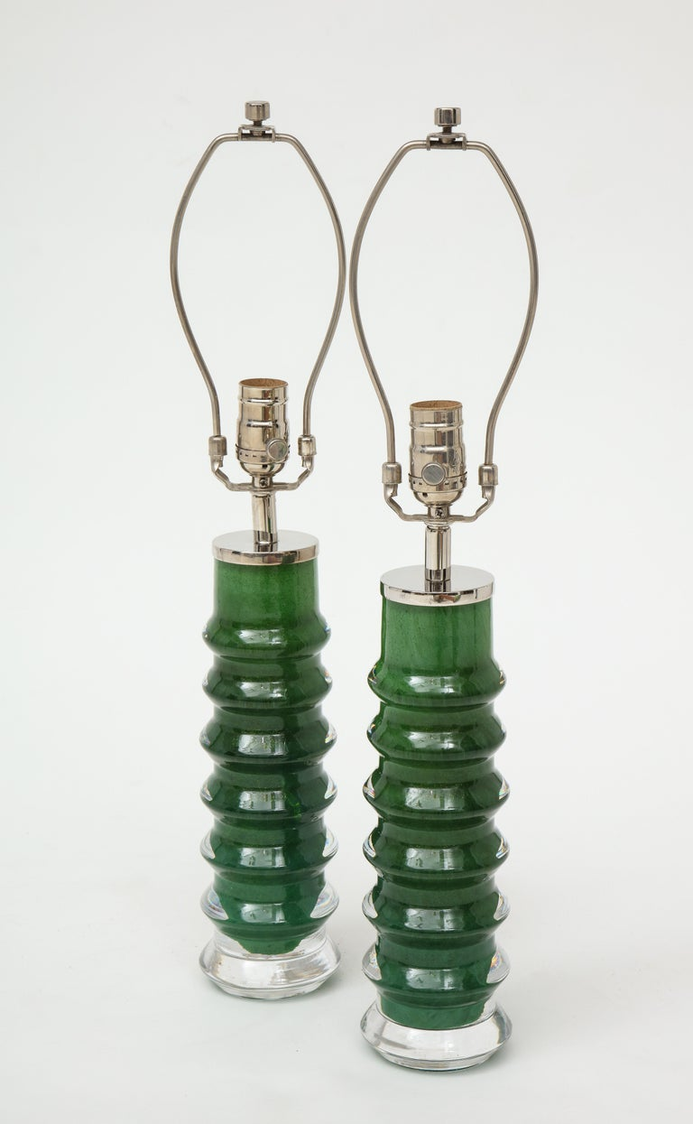 Pair of rare color and form Emerald Green glass crystal lamps with polished nickel hardware. Signed. Rewired for use in the USA. Glass portion is 12.50 inches tall.