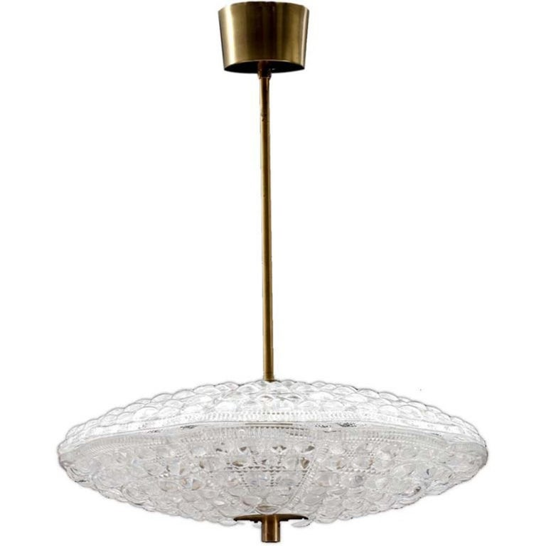Pair of Flying Saucer shaped chandelier in two pieces. Beautiful textured glass with brass fittings. Designed by Carl Fagerlund for the Swedish glass maker Orrefors. Takes five candelabra basebulbs.  Existing old wiring, rewiring complementary, let