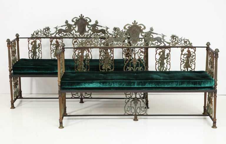 A rare pair of bronze and iron Oscar Bach benches having a centralized shield form plaque framed by centaurs battling serpents, circa 1920. From a Nyack, NY waterfront mansion estate. Restored with reupholstered seats in green velvet.