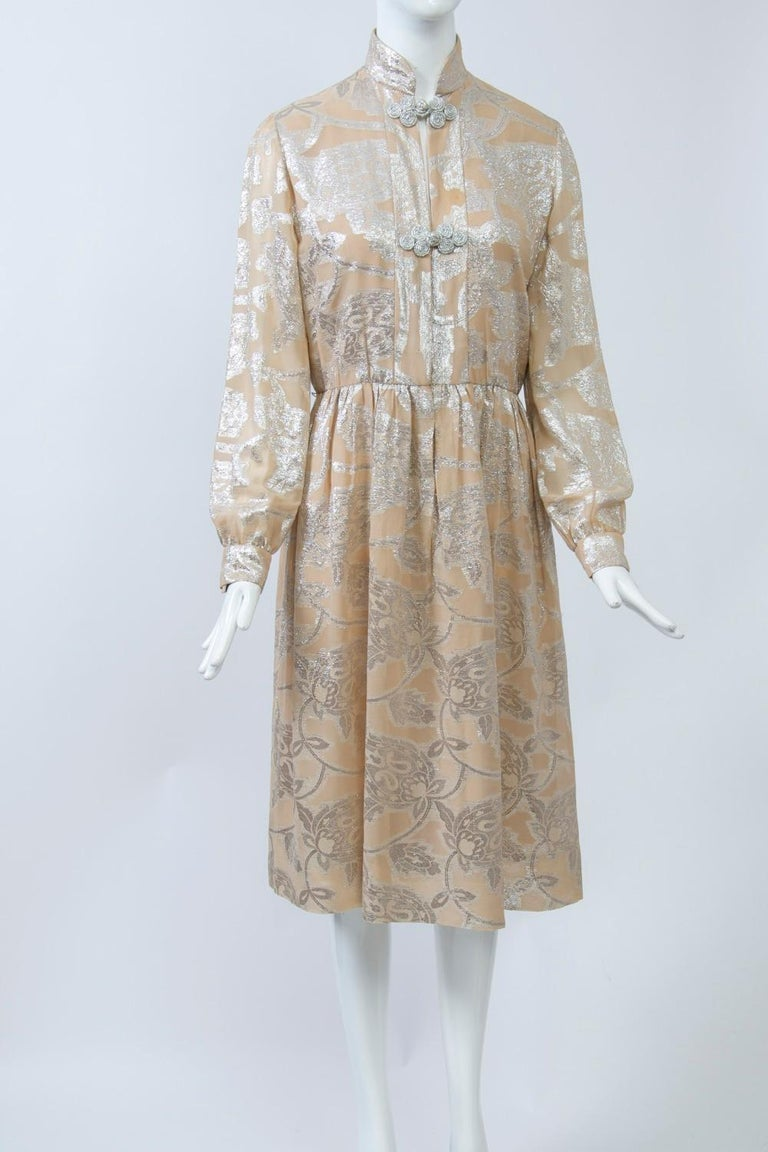 Oscar de la Renta dress c.1970 crafted of a sheer beige fabric shot through with silver metallic thread in a large abstract floral pattern. Modified shirtwaist style with front opening that featrues 2 silver thread frog closures, one at the mandarin