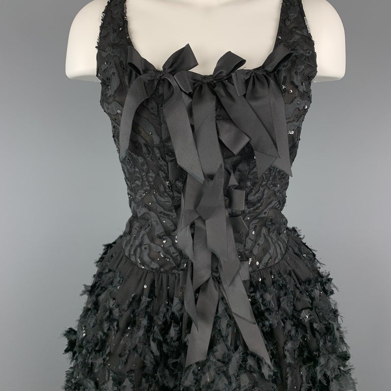 Sleeveless OSCAR DE LA RENTA cocktail dress features a tiger pattern sequin burnout tulle bodice with bow accents, and bubble skirt with frayed ribbon appliques. Circa 2008. Made in USA.  Very Good Pre-Owned Condition. Marked: