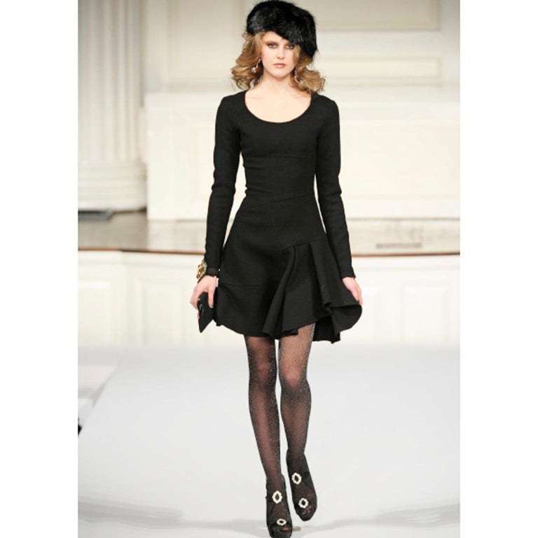 This is a black wool long sleeve dress w/ colorful cuff buttons and asymmetrical seams documented from the Oscar de la Renta Fall/Winter 2010 collection. We love this understated dress because it puts a really unique spin on a classic and