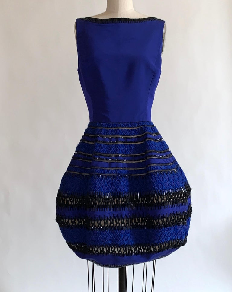 Oscar de la Renta cobalt blue silk dress with embellished skirt. Beading at neckline and throughout skirt. Blue embroidery detail and black ornamental cording at skirt. Back zip.   100% silk.  Lined in 100% nylon.  Size US 6, may run small, see
