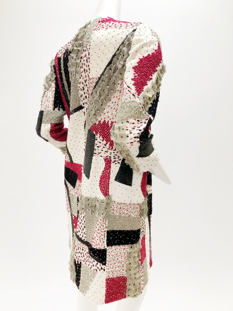 A lovely Oscar De la Renta  beaded and sequined silk and wool patchwork 3/4 length evening jacket in a red, black, gray and white color scheme. Scattered gray applique stylized flowers. Lined. No closures or collar. Size 4.